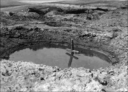 Cross in a flooded shell hole; German amateur picture. Source: http://www.flandersfieldsmusic.com/ww1-photos.html